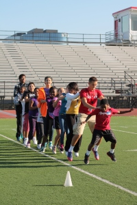6th graders and their high school leaders play team building games on the football field
